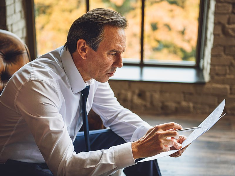 Man debating documents delaying retirement investment opportunities