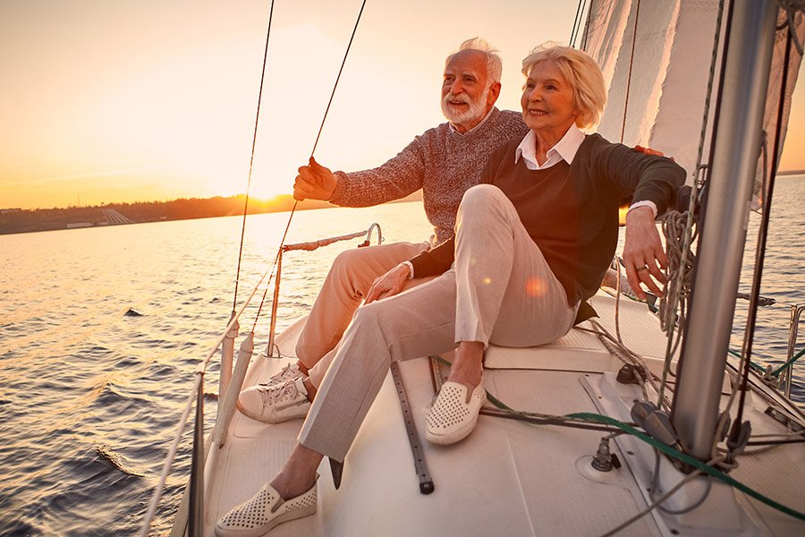 elderly graceful couple taking in the view from their tacht while planning for retirement
